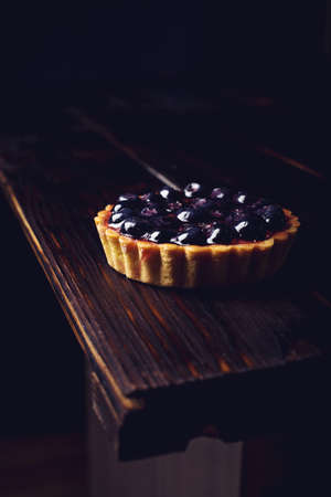 plato del buen comer: En el mini tarta de la baya con los arándanos sobre una mesa de madera sobre fondo oscuro