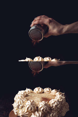 Hand sprinkle cocoa on the Beautiful white cake, a wooden table over dark background