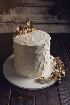topper: white cream cake decorated with a branch with gold leaves on a wooden stand in a rustic style. trends for wedding desserts, food design