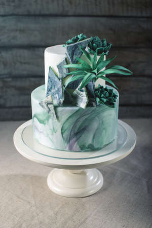 Artwork. Bunk Wedding cake decorated like a stone marble with green flowers and leaves of agave on a background of fabric. food design. trends