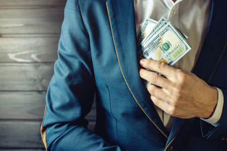 payola: Man businessman, member or officer in a suit puts a bribe in the form of hundred dollar bills in his pocket. the concept of corruption and bribery among high-ranking officials Stock Photo