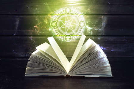 bewitched: Open magical book with pages like a fan is on the table out comes a colorful light and magic sign. The concept of fantasy and witchcraft Stock Photo