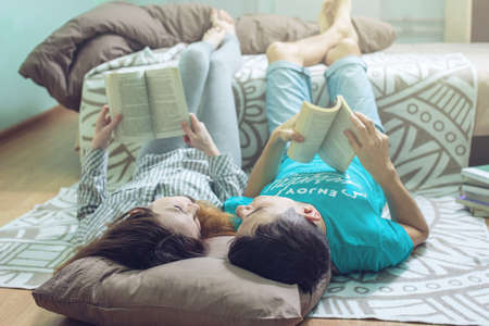 Couple in love girl and guy lying on the floor and lifting legs nice reading. the concept of education and the popularization of reading