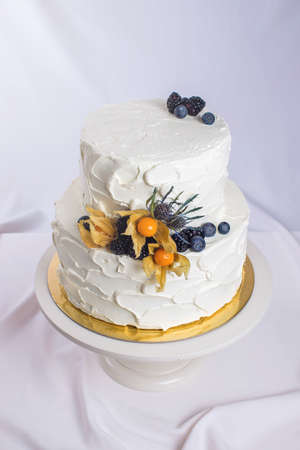 topper: two-tiered white cream cake decorated with berries in a rustic style. trends for wedding desserts, foot design Stock Photo