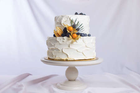 nightshade: two-tiered white cream cake decorated with berries in a rustic style. trends for wedding desserts, foot design Stock Photo