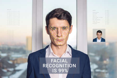 Recognition of a male face by layering a mesh and the calculation of the personal data by the software. Biometric verification and identification Stock Photo