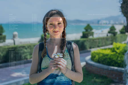 Recognition of a female face by layering a mesh and the calculation of the personal data by the software. Biometric verification and identification