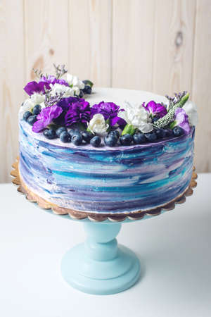 Colorful wedding cream cake with lovely purple flowers adorn the top and blueberries