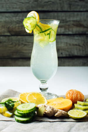 Cool fresh fruit lemonade with ice in hurricane glass with lemon and cucumber. The concept of summer drinks cocktails Stock Photo