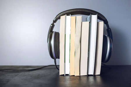 Black headphones on a stack of books. The concept of audiobooks
