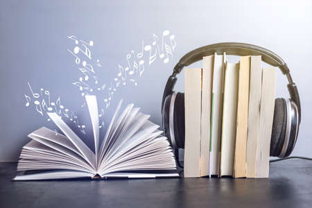 Black headphones on a stack of books near open book and flying notes. The concept of audiobooks 版權商用圖片