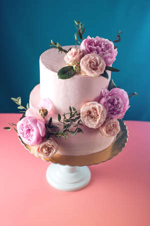 Bunk pink cream wedding cake decorated with fresh roses on a blue background. food design. trends.