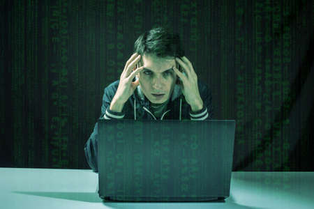 cyber terrorism: young hacker in the dark breaks the access to steal information and infect computers and systems. concept of hacking and cyber terrorism