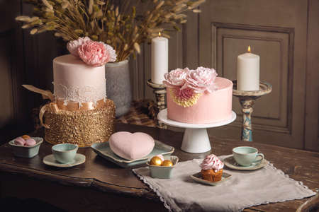 Luxury wedding table with a beautiful pink cake decorated with mastic and rose gold in antique classic expensive interior. the concept of chic wedding desserts Reklamní fotografie