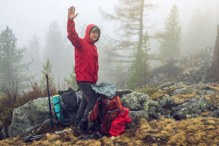 hiker travels in the mountain forest in the mist with a backpack welcomes all friends. the concept of travel and Hiking in wild places of nature Banco de Imagens