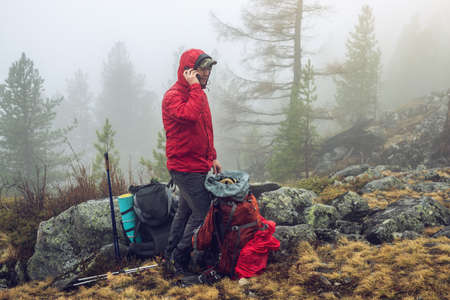 Hiker travels in the mountain forest in the mist with a backpack and trying to find a mobile connection. the concept of travel and Hiking in wild places of nature