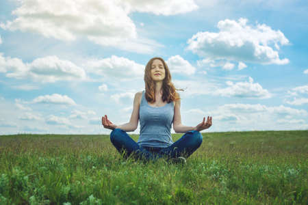 Woman traveler sitting on the meadow with green grass under blue sky with clouds in the Lotus position. Meditating in complete tranquility and freedom Stock Photo