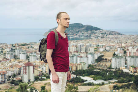 Man traveler with backpack explores the city looking at the panoramic view of the city and the coast. The concept of travel is discovering new places