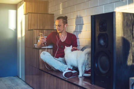 earbud: Handsome man, a music lover listens to music with headphones with a mobile phone and playing with a white cat. Enjoying music is fun and communicates on the Internet at home. The concept of creative and positive lifestyle