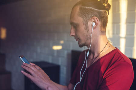Handsome man, a music lover listens to music with headphones with a mobile phone in a modern interior against the media and large speakers. Enjoying music is fun and communicates on the Internet at home. The concept of creative and positive lifestyle Stock Photo
