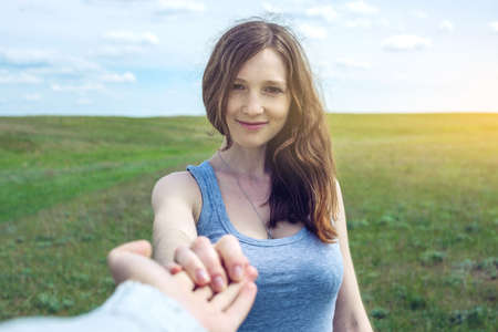 Follow me, Attractive brunette girl holding the hand of the leads in a clean green field, steppe with clouds. The concept of the journey to the meeting of the nature