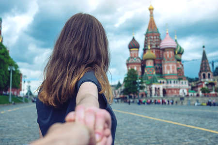 Follow me, Attractive brunette girl holding the hand leads to the red square in Moscow. The concept of the journey to the meeting of new discoveries in Russia