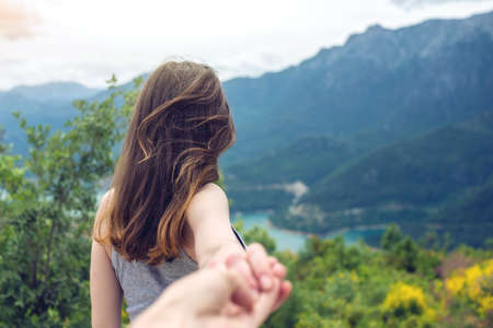 Follow me, Attractive brunette girl holding hands with leads in mountain valley with river. The concept of the journey to the meeting of new discoveries
