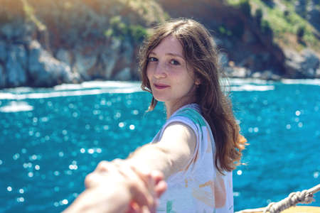 Follow me, Attractive brunette girl holding the hand leads to the mountains and the blue sea. The concept of the journey to the meeting of new discoveries