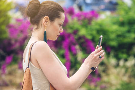 Woman traveler with backpack makes a photo on your smartphone outdoors on the background of nature and flowering trees. The concept of connection and communication in the journey. Stock Photo