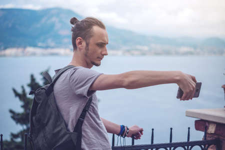 Man traveler with backpack makes a photo on your smartphone outdoors with mountains in the background. The concept of connection and communication in the journey. Stock Photo