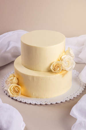stands: Beige 2 tiered wedding cake decorated with mastic roses stands on the table on fabric background