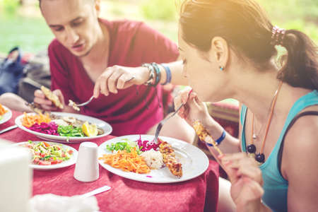 young couple eats vegetables and fish outdoors in a cozy restaurant on the water during travel, opens new kitchen Stock Photo