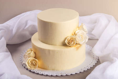 sugarpaste: Beige 2 tiered wedding cake decorated with mastic roses stands on the table on fabric background