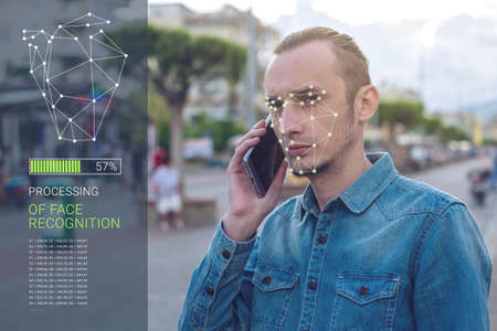 Biometric verification. Modern young man with the phone. The concept of a new technology of face recognition on polygonal grid is constructed by the points of IT security and protection Фото со стока - 83756842