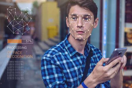 Biometrische Verifikation. Moderne junge Mann mit dem Telefon. Das Konzept einer neuen Technologie der Gesichtserkennung auf dem polygonalen Gitter wird durch die Punkte der IT-Sicherheit und des Schutzes konstruiert Standard-Bild - 83755442