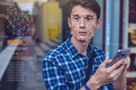 Biometric verification. Modern young man with the phone. The concept of a new technology of face recognition on polygonal grid is constructed by the points of IT security and protection