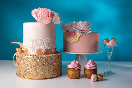 Luxury wedding table with a beautiful pink cake decorated with mastic pink rose and gold on a blue background. the concept of chic wedding desserts