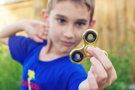 A boy plays with spinner twisting it in his hand on outdoors. Trends in childrens anti-stress toys for attention