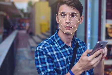 Biometrische verificatie. Moderne jonge man met de telefoon. Het concept van een nieuwe technologie voor gezichtsherkenning op een veelhoekig raster wordt geconstrueerd door de punten van IT-beveiliging en -bescherming Stockfoto