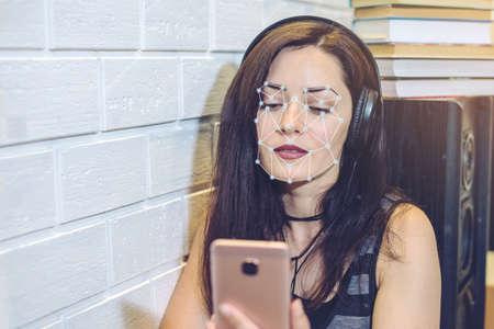 Biometrische verificatie. Moderne jonge vrouw aan de telefoon. Het concept van een nieuwe technologie voor gezichtsherkenning op polygonaal raster is gebouwd door de punten van beveiliging en beveiliging van IT
