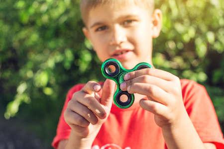 Een jongen speelt met spinner en draait hem in de hand in de buitenlucht. Trends in anti-stress speelgoed voor kinderen ter aandacht Stockfoto