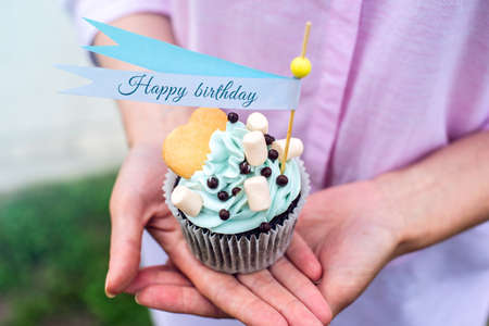 Delicious cupcake with blue cream and marshmallows in the hands of the girls. Sweet gift for birthday and wedding