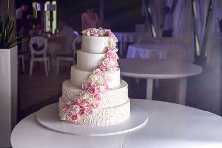 A large tiered wedding cake decorated with pink roses on the table in the restaurant. The concept of festive desserts Stock Photo