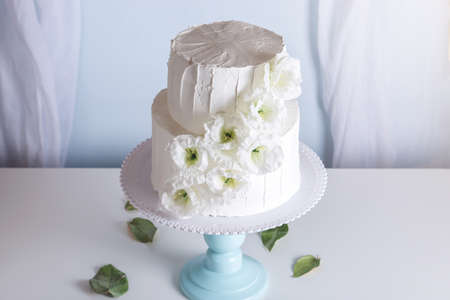 White bunk wedding cake decorated with flowers on a blue bookcase