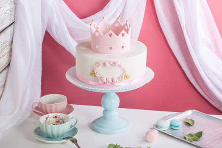 Cute pink cake with a crown on the table with cups to the birthday for a Princess