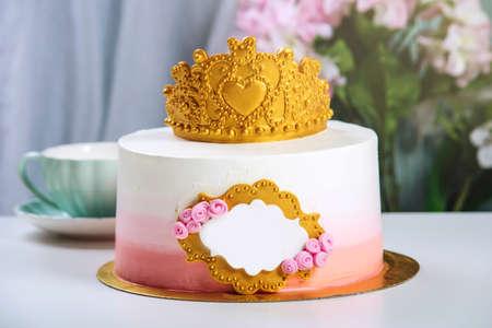 Pastel lindo con una corona de oro en la mesa con tazas para el cumpleaños de una princesa. Lugar para el texto Foto de archivo - 83522117
