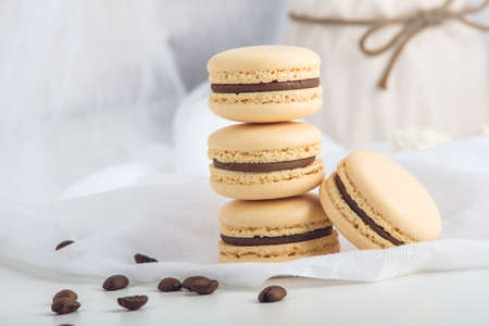 Coffee macarons with chocolate. French delicate dessert for Breakfast in the morning light