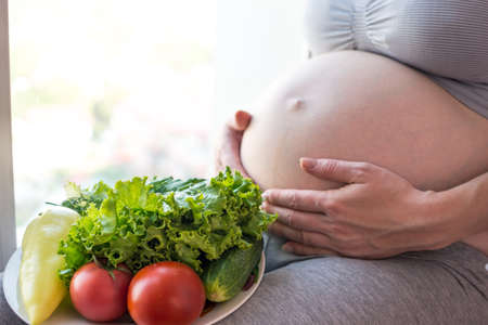 beautiful womb: A pregnant woman with belly holding a plate with vegetables in hands. The concept for weight control and healthy eating during pregnancy Stock Photo