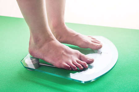 Female feet standing on electronic scales for weight control. The concept of slimming and weight loss Stock Photo