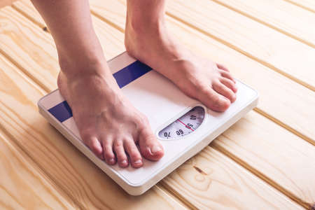 Female feet standing on mechanical scales for weight control on wooden background. The concept of slimming and weight loss